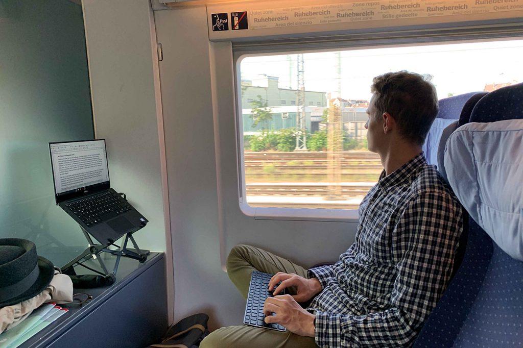 Mann arbeitet während der Zugfahrt am Laptop