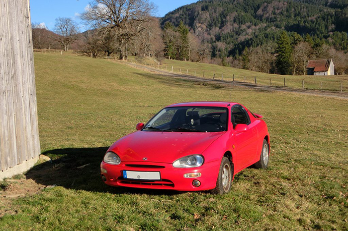 Roter Mazda MX 3 auf einer Wiese