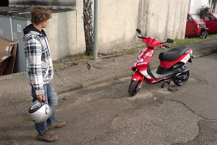 Junger Mann steht einem roten Roller gegenüber
