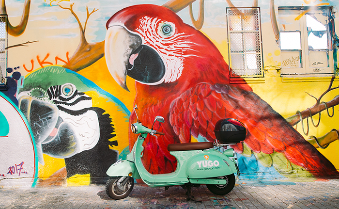 Mint-grüner Elektroroller vor Graffiti-Wand