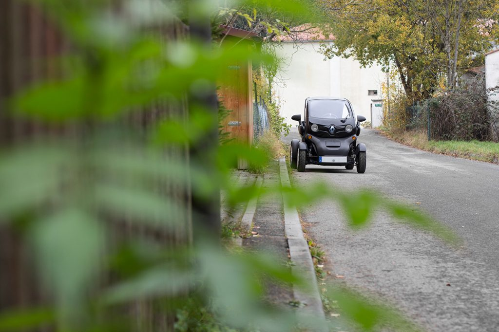Das Elektrische Leichtfahrzeug Renault Twizy hinter unscharfen Blättern.