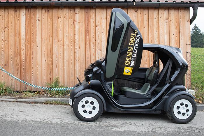 Renault Twizy mit Ladekabel vor Holzhaus.