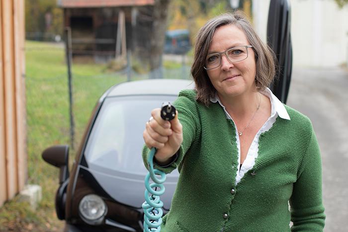 Frau mit Ladekabel des Renault Twizy