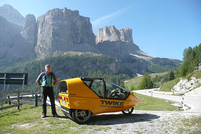 Mann steht neben seinem Twike in den Dolomiten