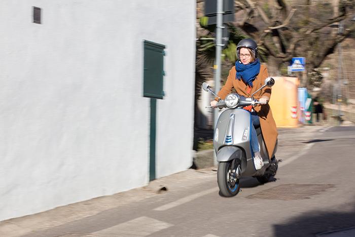 Junge Frau fährt mit der elektrischen Vespa