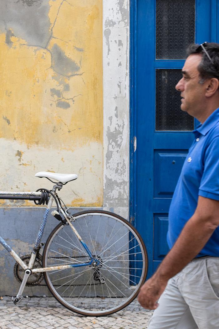 Rennrad vor Hauswand und ein vorbeilaufender Mensch im Anschnitt