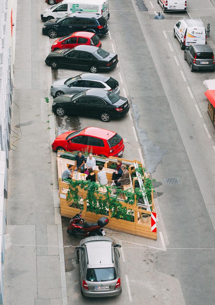 Ein kleiner Garten mit Bänken zwischen parkenden Autos in Wien