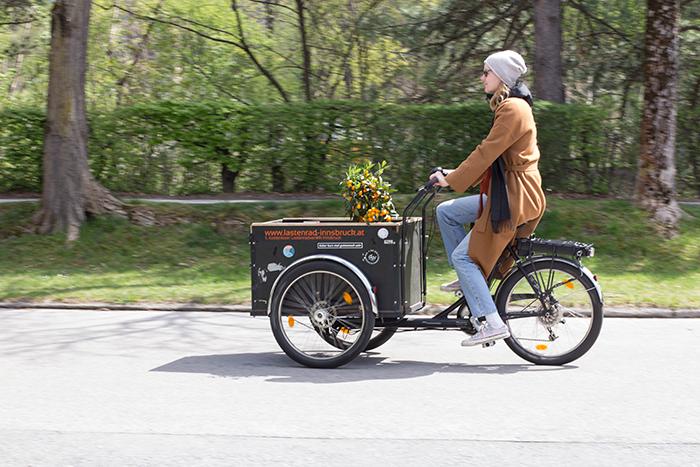 Junge Frau mit Lastenrad fährt vorbei