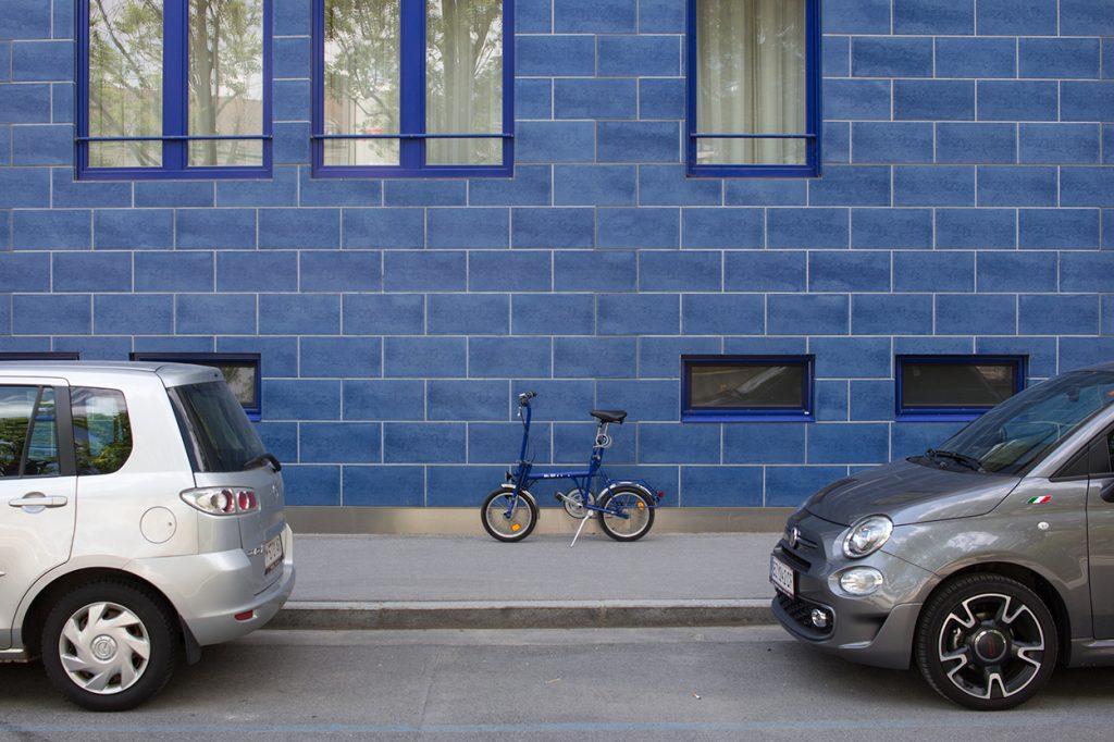 Blaues Klapprad zwischen parkenden Autos