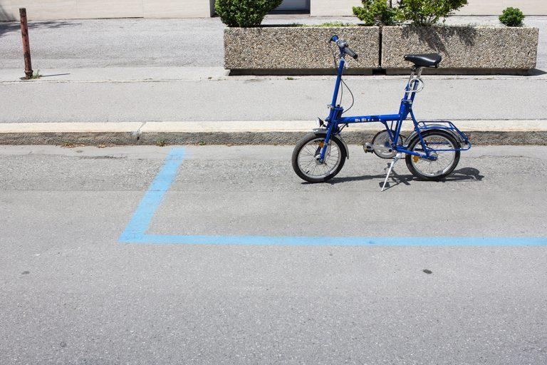 Blaues Klapprad auf leerem Parkplatz