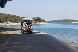 Kleines elektrisches Fahrzeug auf einer Küstenstraße