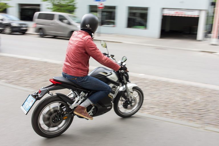 Mann mit roter Lederjacke fährt auf dem E-Motorrad vorbei.