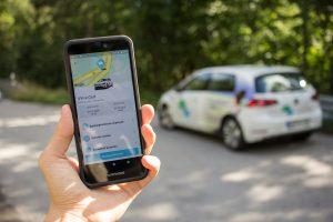 Smartphone im Vordergrund und Auto unscharf im Hintergrund