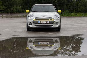 Der elektrische Mini Cooper SE von vorne spiegelt sich in einer Pfütze