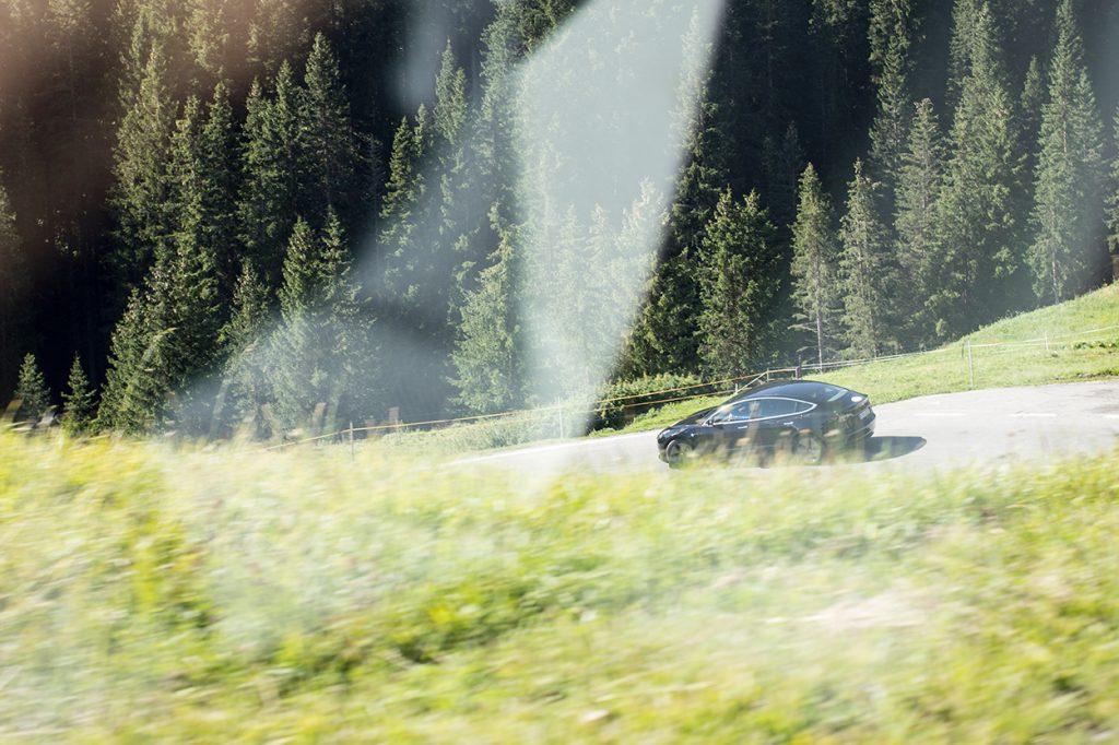 Schwarzer Tesla auf einer Bergstraße aus fahrendem Auto fotografiert.