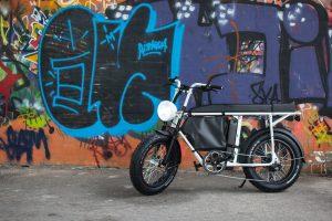 Das elektrische Mofa von Urban Drivestyle vor einer Wand mit Graffiti