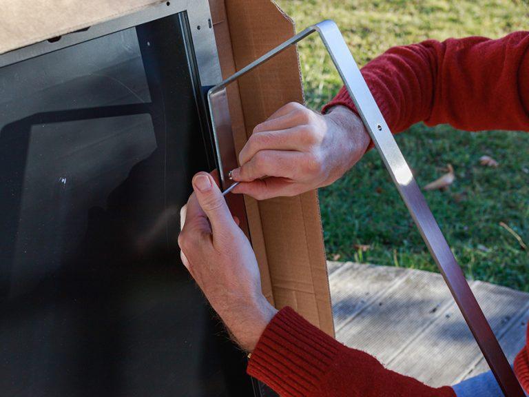 Zwei Hände montieren die Standbeine ans Solarpaneel