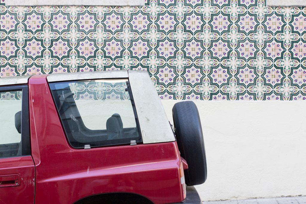 Geparktes Auto vor einer Wand mit Fliesen