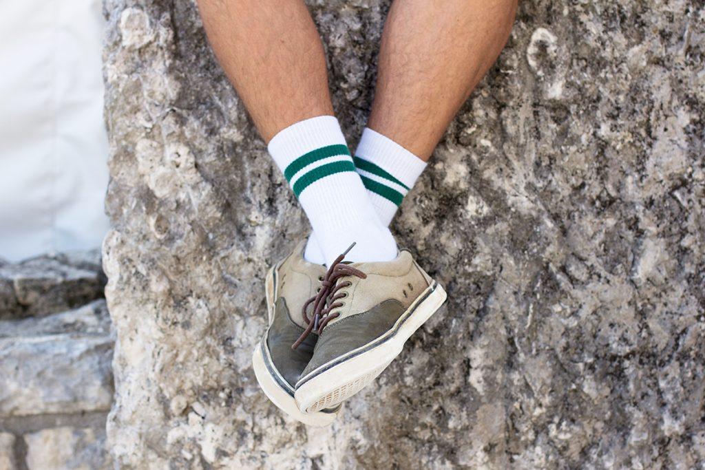Verschränkte Füße mit weißen Socken mit grünen Streifen