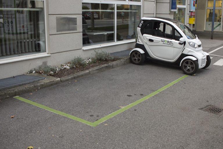 Ein kleines elektrisches Fahrzeug in einer normalen Parklücke