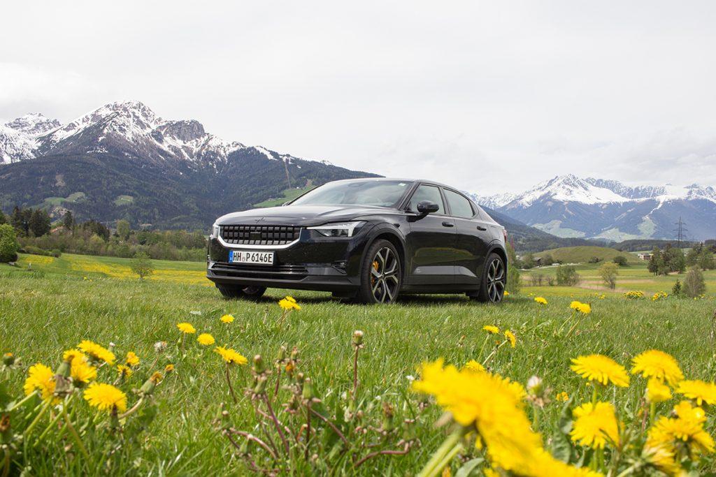 Der Polestar 2 an einer Blumenwiese vor den Alpen