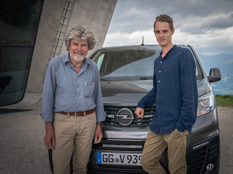 Reinhold Messner und Autor Felix Strohbach stehen neben einem Elektro-Van von Opel
