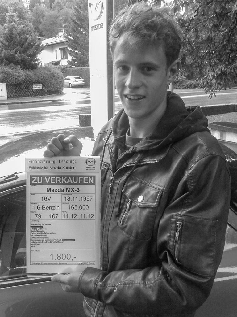 """Autor Felix Strohbach mit dem """"Zu Verkaufen""""-Schild vor seinem ersten eigenen Auto"""