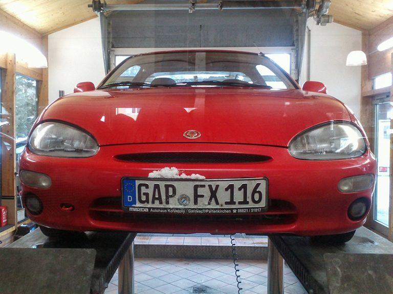 Roter Mazda auf der Hebebühne in der Werkstatt