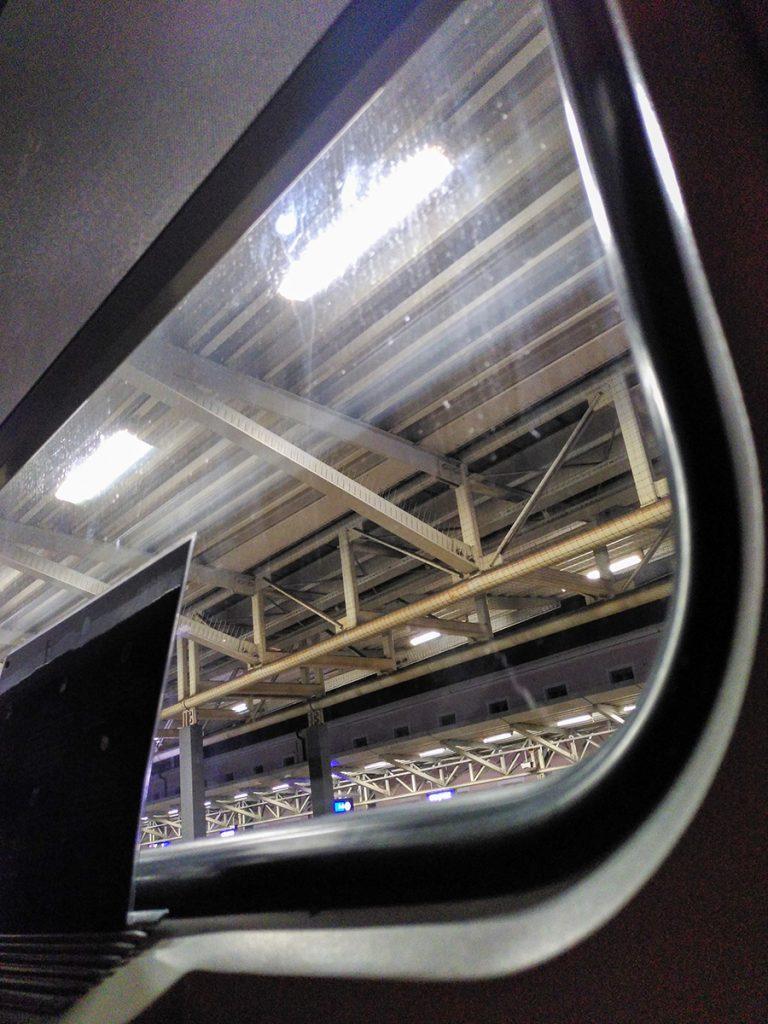 Blick aus dem Fenster im Liegen auf einen Bahnsteig