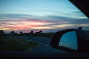 Blick aus dem offenen Autofenster bei Sonnenuntergang