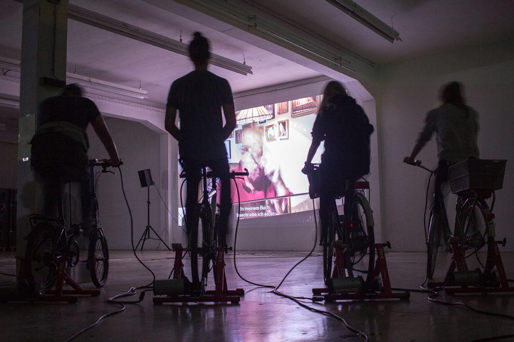 Silhouetten von Radfahrenden vor einer Kinoleinwand
