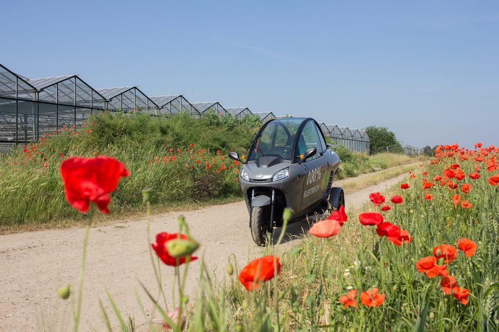 Kabinenroller Carver an einer Blumenwiese mit roten Tulpen